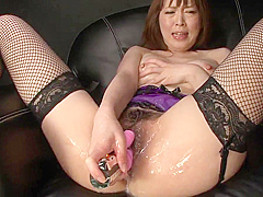 Brunette in fishnet stockings fucks herself with a toy